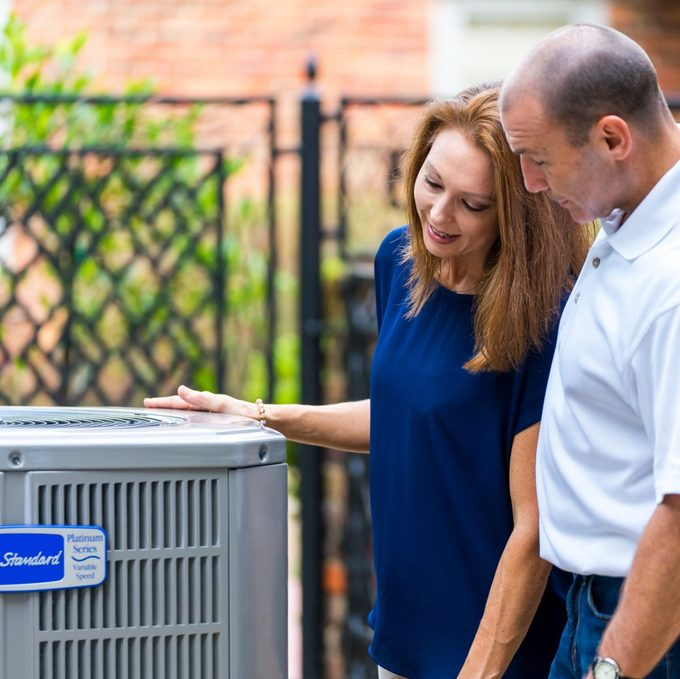 Two people checking out an air conditioner