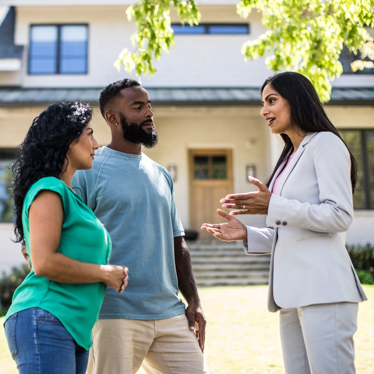 Couple meeting with real estate agent in front of home