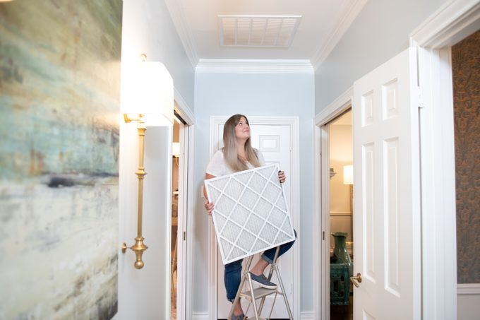 Woman climbing up a small ladder in the corridor holding a duct cover for her home's ventilation system