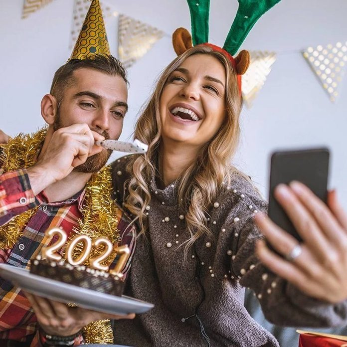 Couple celebrating Christmas at home, holding chocolate cake with lit candles shaped as numbers 2021 and having a video call with friends new years eve