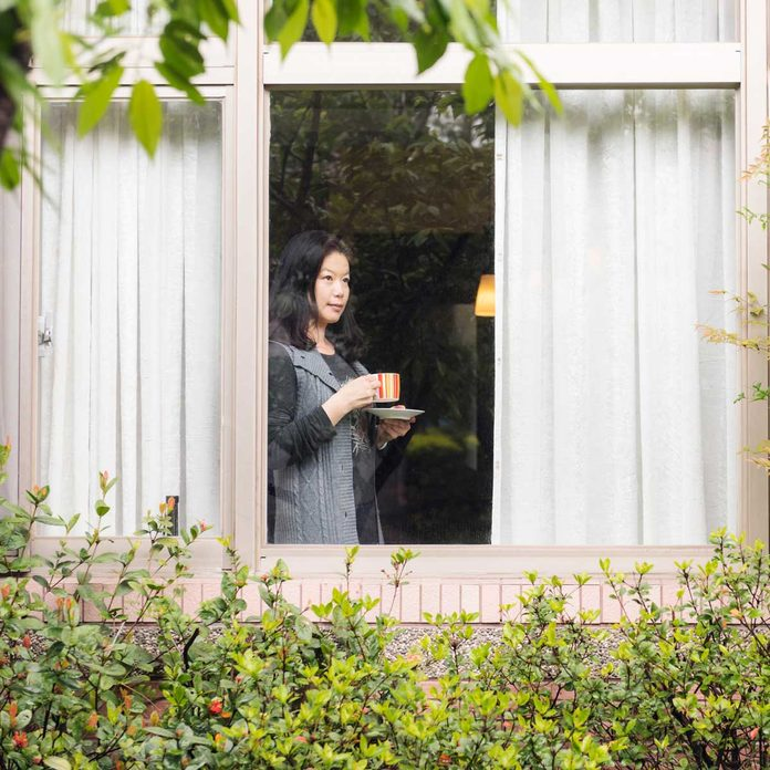 Woman drinking coffee and looking out the curtains