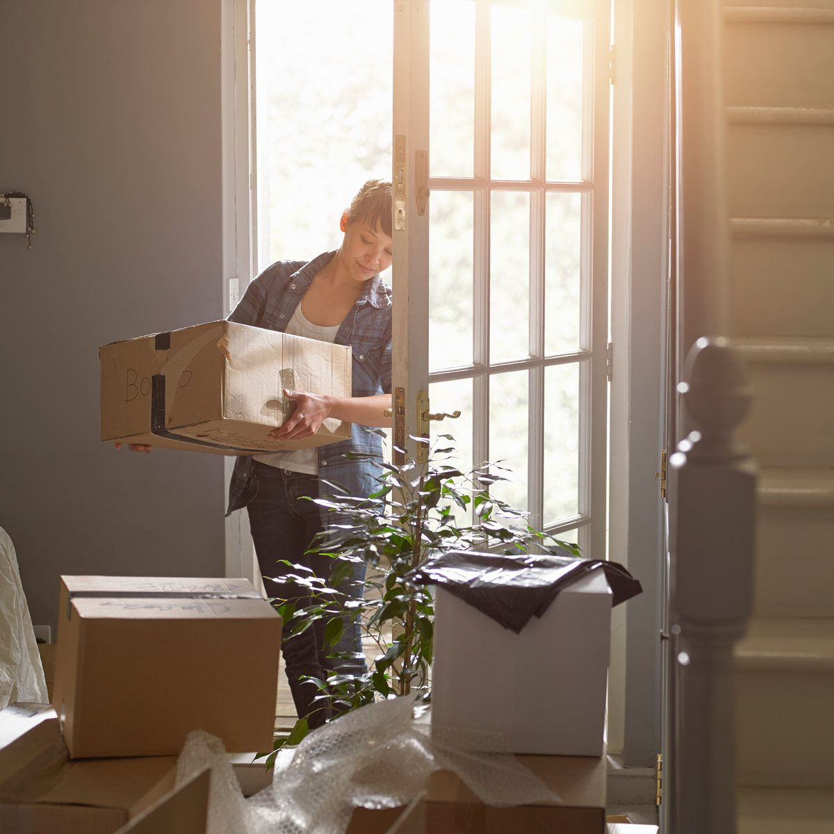 moving boxes And woman carrying a packing box into her new home Gettyimages 495164449