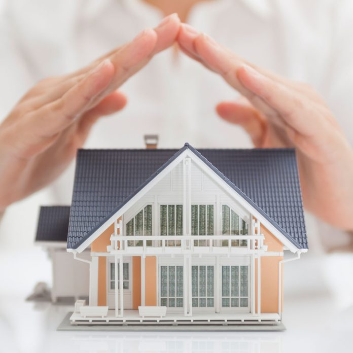 Home Warrenty Concept: hands covering a model house