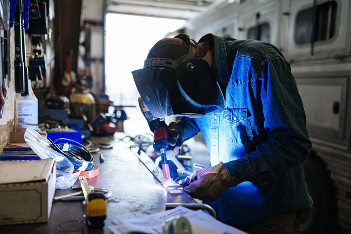 DIY Welder working in his garage at home with proper supplies