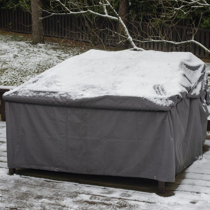 Patio furniture Cover protecting outdoor furniture from snow, close up.