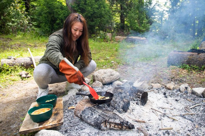 woman using a spatula while cooking over a campfire