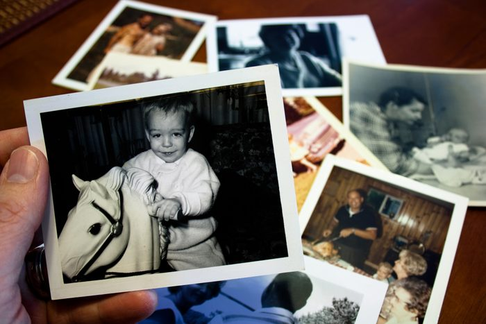 Hand holds Vintage photograph of child with hobby horse toy with other printed photos on the table in the background