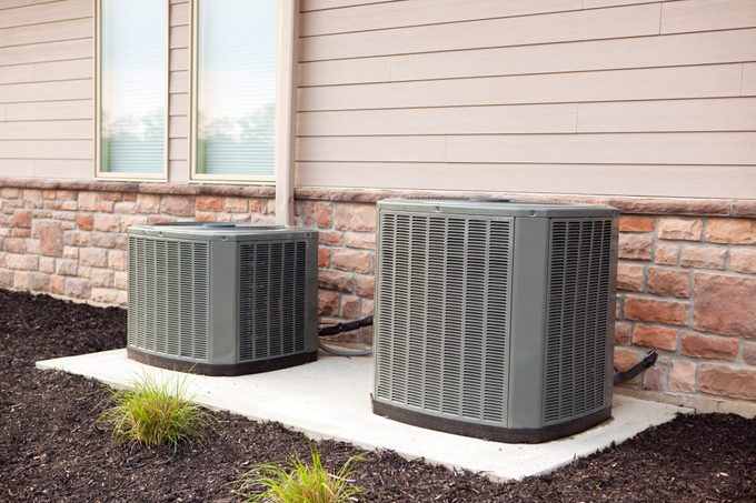 two central air conditioning units outside of house