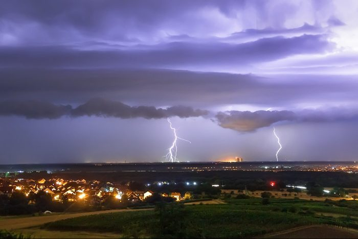 heat lighting off in the distance on the horizon of a landscape with homes at night