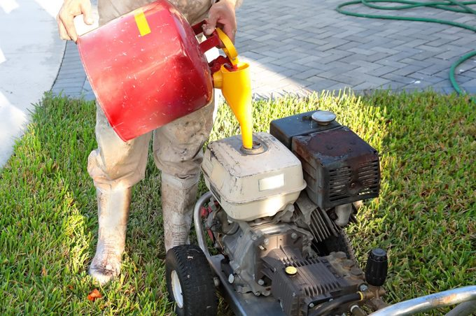 Series:unrecognizable Worker Filling A Power Washing Machine With Gasoline