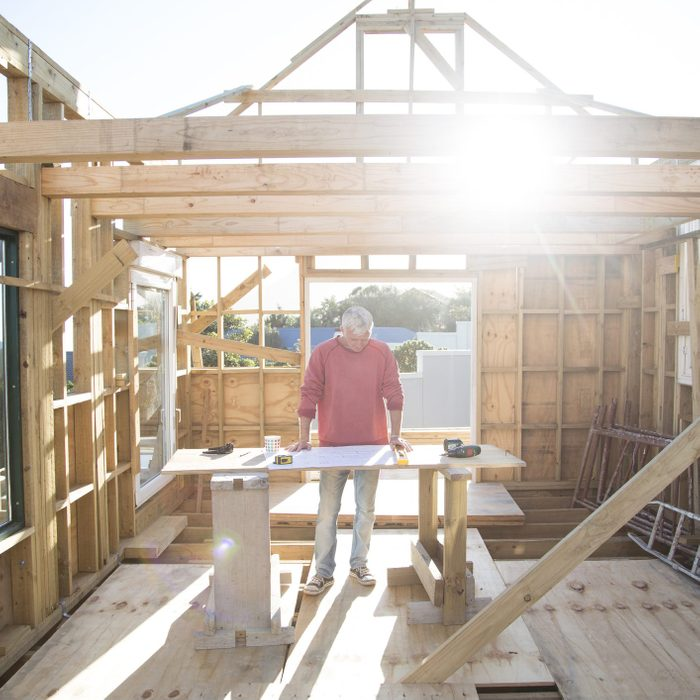 man looking at plans for house that is being built