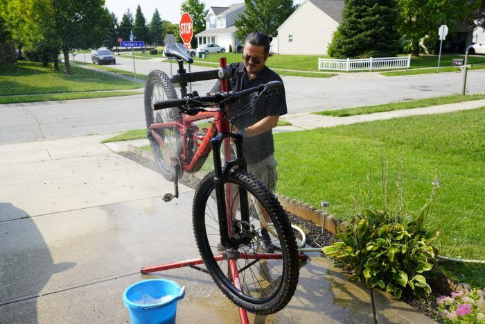 man cleaning his bike with a hose in the driveway
