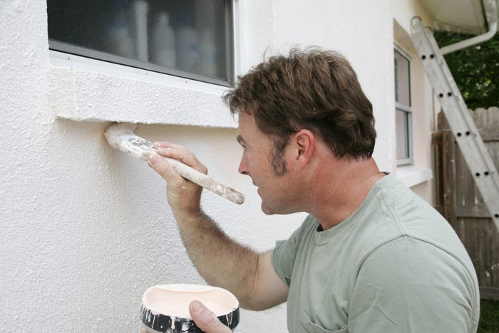 man painting the stucco exterior of a home