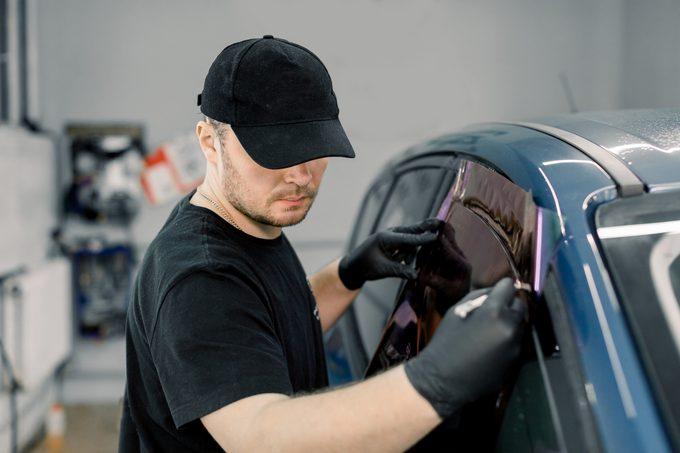 man applying window tint to car window in the shop