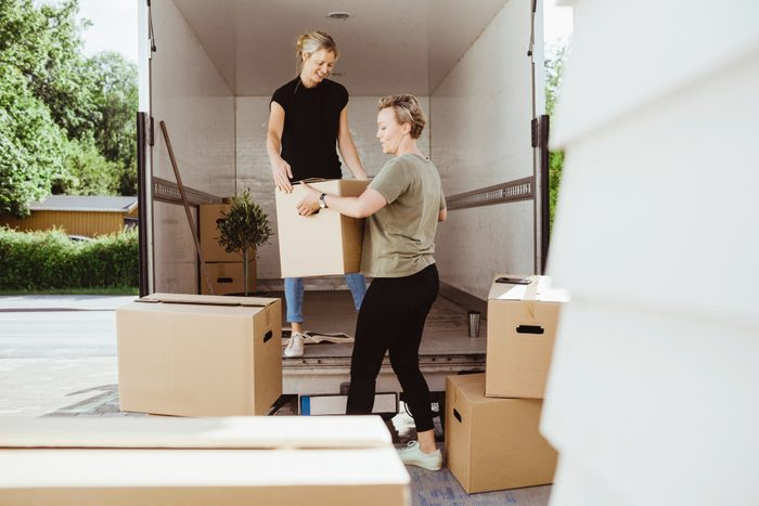 women loading moving boxes onto moving truck