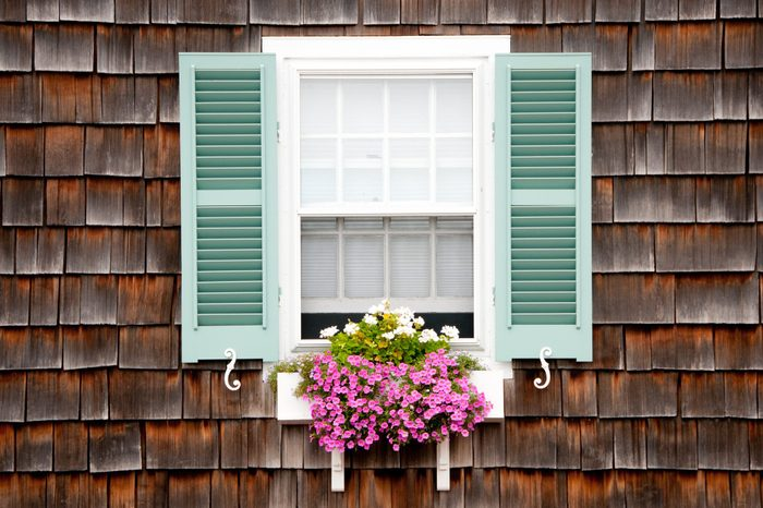 Old beach cottage with wood shake siding. Window with turquoise shutters and white wooden window box and trailing pink and white flowers in summer.