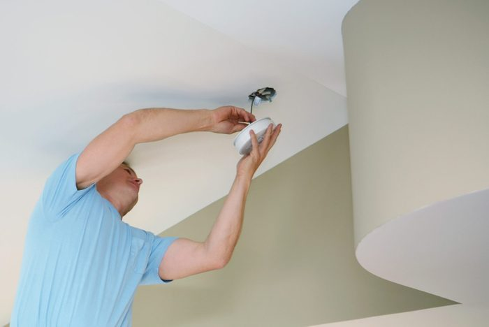man Installing a wired Smoke Detector in home