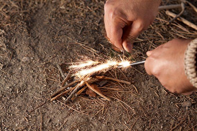 man starting a fire with flint