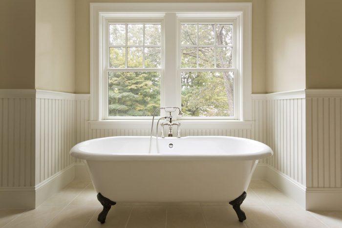 Clawfoot bathtub near the window in bathroom