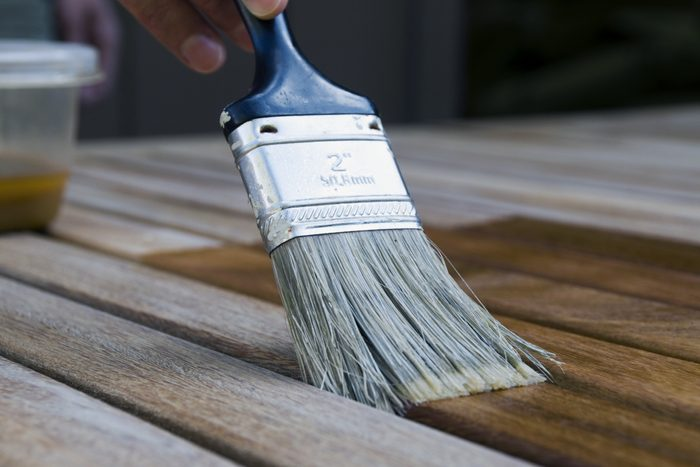 close up of paintbrush staining wood