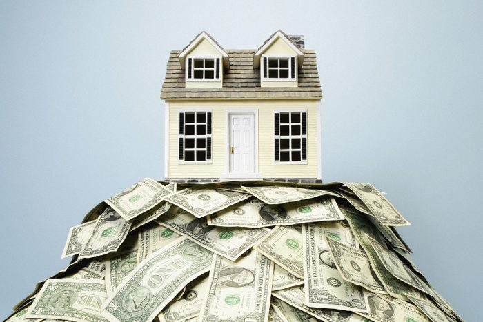 Model home resting on top of US paper currency representing homeowners insurance