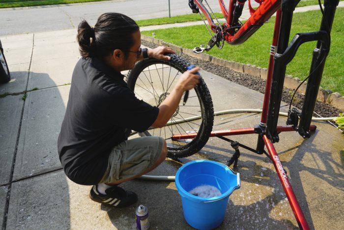man washing the wheels of his bike